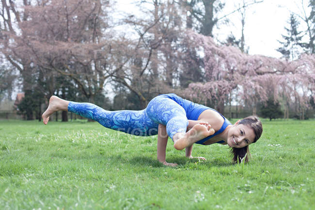 Woman doing yoga handstand in park on lawn — Stock Photo