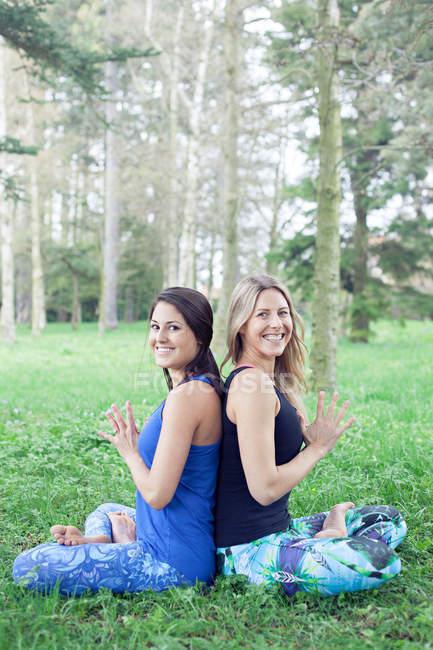Dos mujeres sentadas en loto posan espalda con espalda en el parque - foto de stock