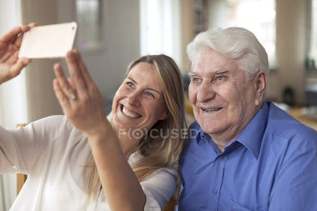Woman taking selfie with grandfather — Stock Photo