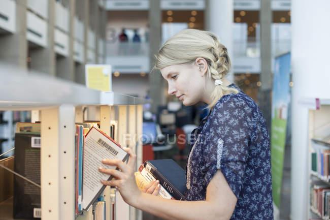 Femme blonde en tenant des livres de bibliothèque étagères — Photo de stock