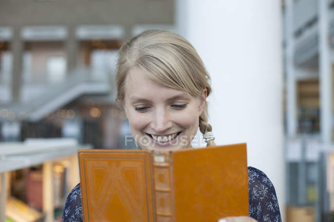 Portrait of blonde woman smiling and holding open book in library — Stock Photo