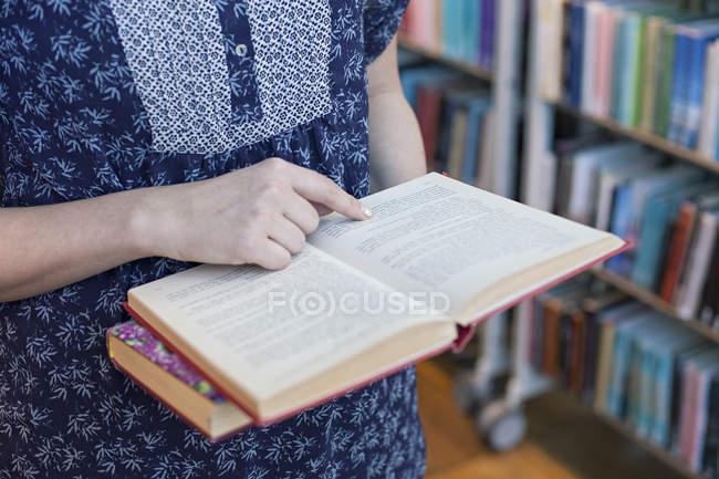 Обрезанный вид женщина проведение открытой книги в библиотеке — стоковое фото