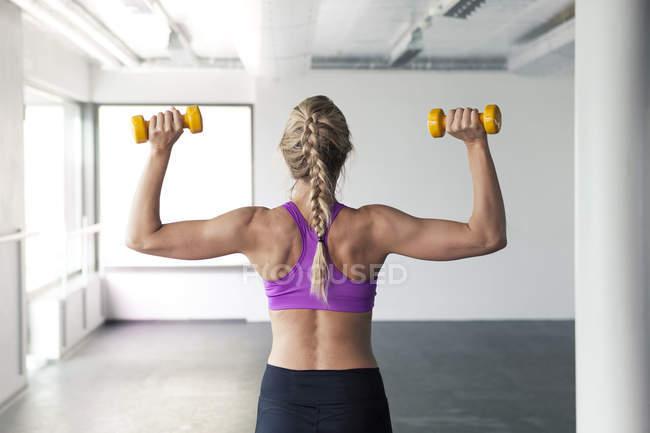 Woman lifting dumbbells — Stock Photo