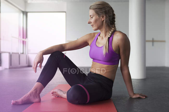 Femme assise sur le tapis fitness — Photo de stock