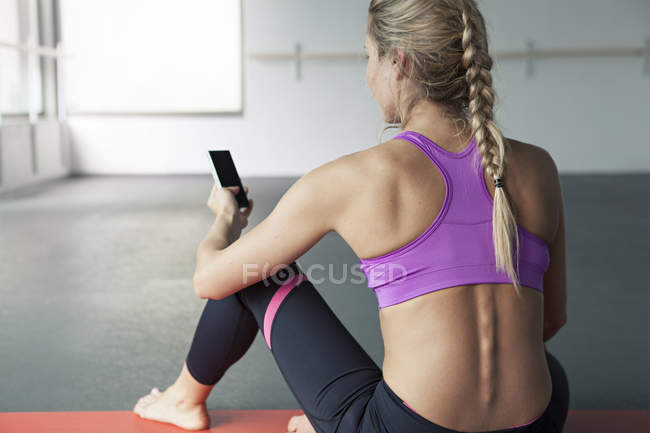 Woman using smartphone on fitness mat — Stock Photo
