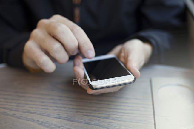 Close-up view of male hands holding smartphone in train — Stock Photo