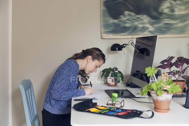 Seitenansicht der Frau arbeiten am Schreibtisch im Wohngebäude — Stockfoto