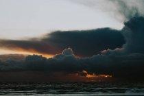 Vue lointaine du paysage nuageux au-dessus de la côte océanique au coucher du soleil — Photo de stock
