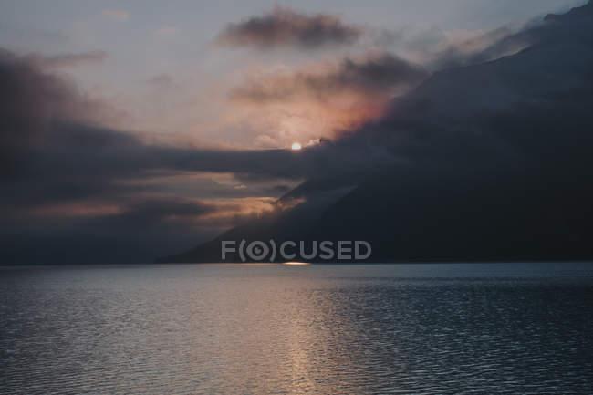 Vue distante du coucher de soleil sur les montagnes dans les nuages et la mer — Photo de stock