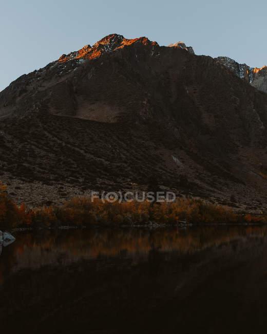 Vista distante Montanha escura e lago ao pôr do sol — Fotografia de Stock