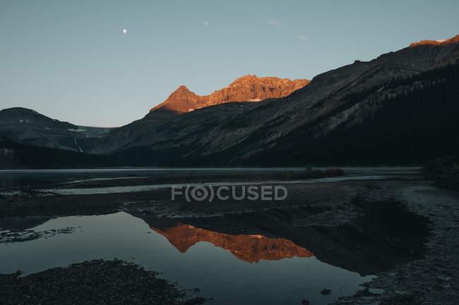 Vue éloignée des montagnes allégé en réfléchissant coucher de soleil au Bow lake, Alberta, Canada — Photo de stock