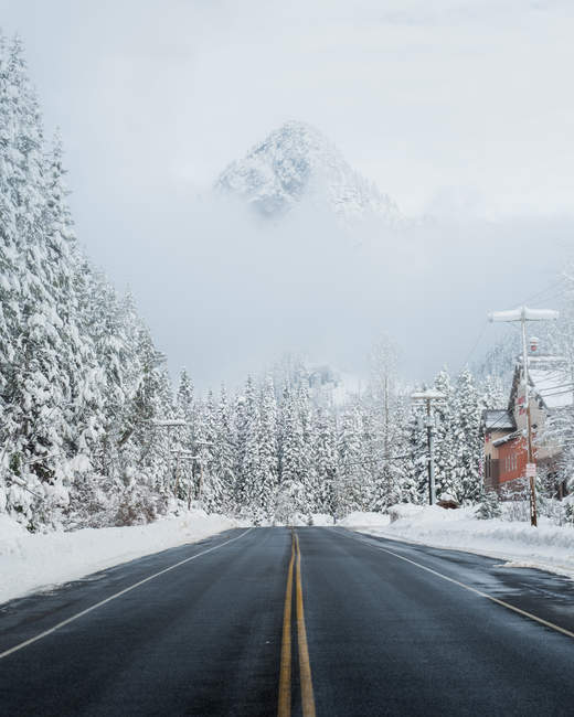 Daytime view of mountain road with snowy forest and houses, Snoqualmie Pass, Cascade Range, Washington — Stock Photo