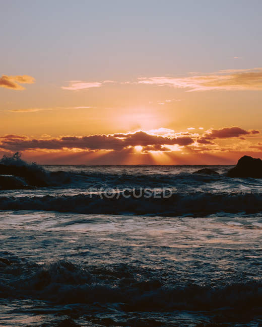 Distant view of colorful sunset and seascape with waves on beach — Stock Photo