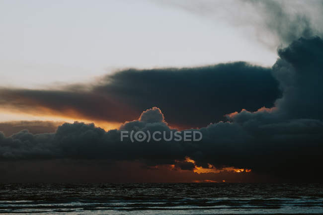 Distant view of cloudscape over ocean coast at sunset — Stock Photo