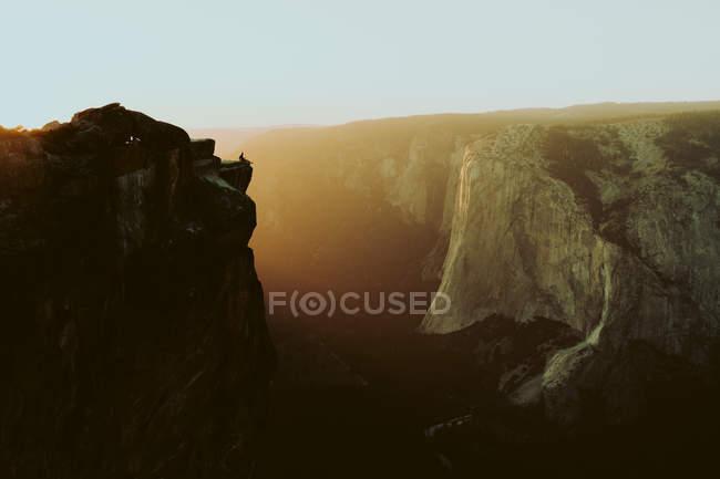 Vista in lontananza della persona seduta su una roccia ripida nelle montagne al tramonto. Taft Point, Parco nazionale Yosemite, California, Stati Uniti — Foto stock