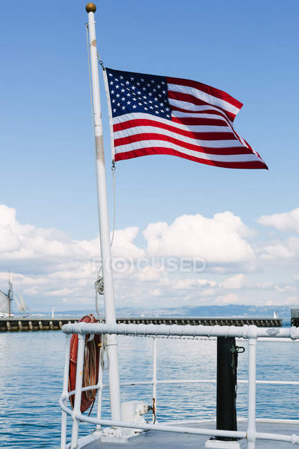 American flag waving on seascape — clear sky, building