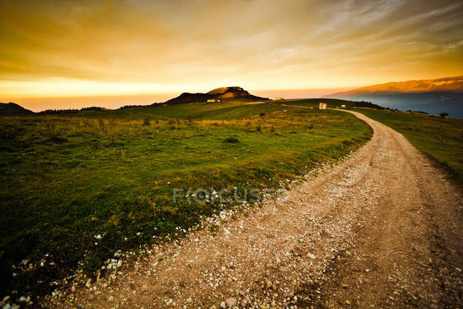 Route de campagne en montagne au coucher du soleil — Photo de stock