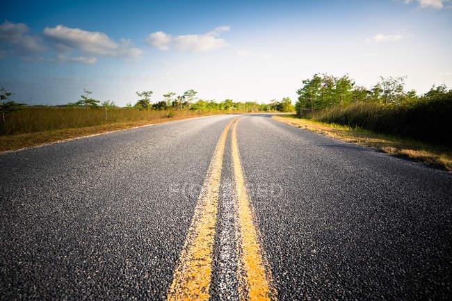 Double ligne jaune sur la route sinueuse — Photo de stock