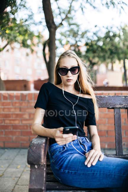 Ragazza in occhiali da sole in possesso di smartphone — Foto stock