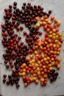 Fresh red and yellow cherries on white marble surface — Stock Photo