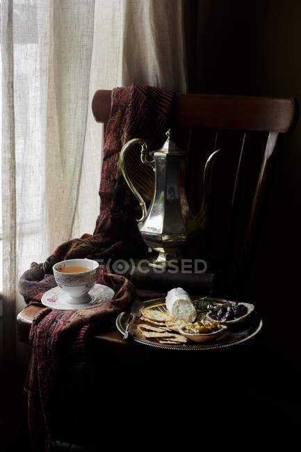 Plateau de fromage avec craquelins et chutney sur chaise avec tasse de thé et théière vintage — Photo de stock
