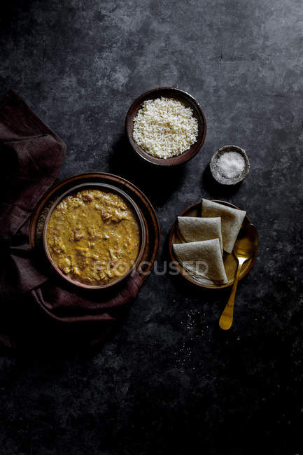 Chicken Tikka Masala with rice in bowl on black surface — Stock Photo