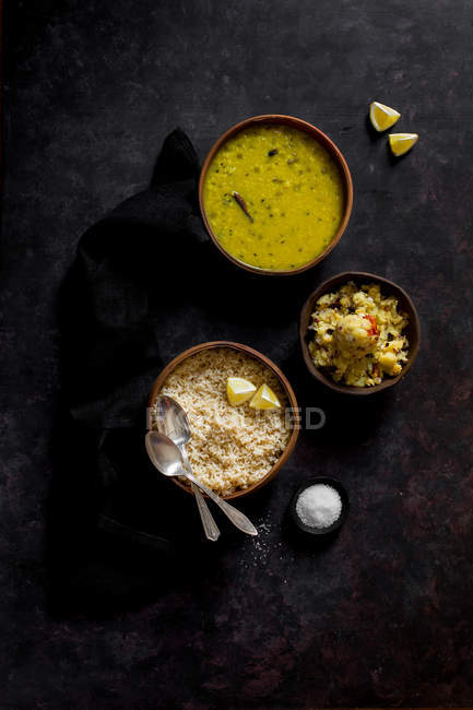 Dal soup with brown rice and mashed potato in bowls on dark grey surface — Stock Photo