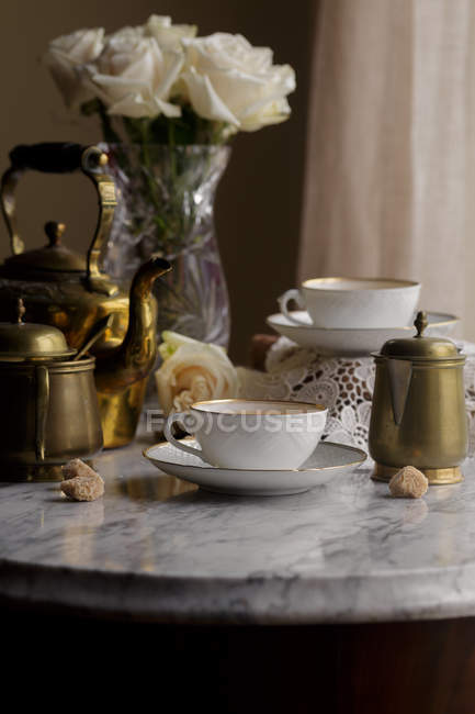 Tea in cups and vintage teapot on white marble tabletop — Stock Photo