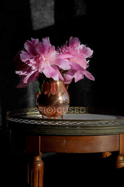 Fresh cut pink peonies in vintage copper vase — Stock Photo
