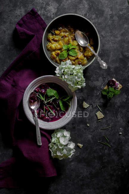 Compotas de uva branca e preta em taças na superfície cinzenta com tecido violeta — Fotografia de Stock