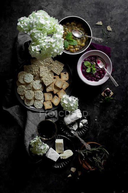 Galletas con queso y mermeladas de uva en fondo gris - foto de stock