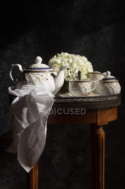Tea-service and fresh flowers on small vintage table — Stock Photo