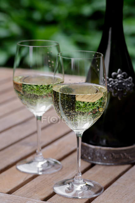 Glasses and bottle of white wine on wooden garden table — Stock Photo