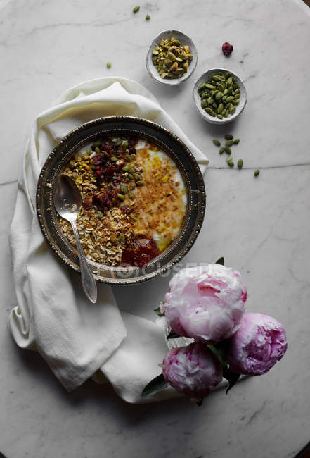 Bowl of yogurt with oats and seeds on table with peonies — Stock Photo