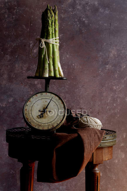 Bunch of green asparagus on old-fashioned scales — Stock Photo