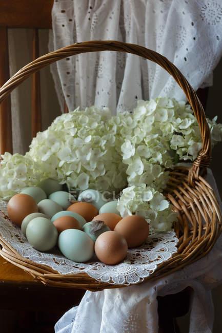 Барвисті яйця в кошик з свіжі Квіти зрізані — стокове фото
