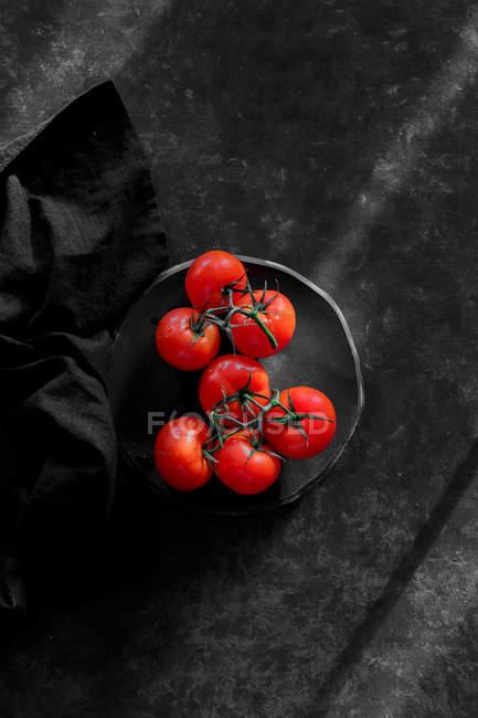 Свіжий червоний помідори на тарілку, на чорній поверхні — стокове фото