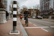 Homme et femme équitation bicyclettes par la route, le paysage urbain sur fond — Photo de stock