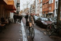 People riding bicycles on old town street, Amsterdam, Netherlands — Stock Photo