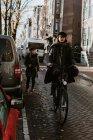 Vélo femme dans rue typique d'Amsterdam, regardant la caméra — Photo de stock