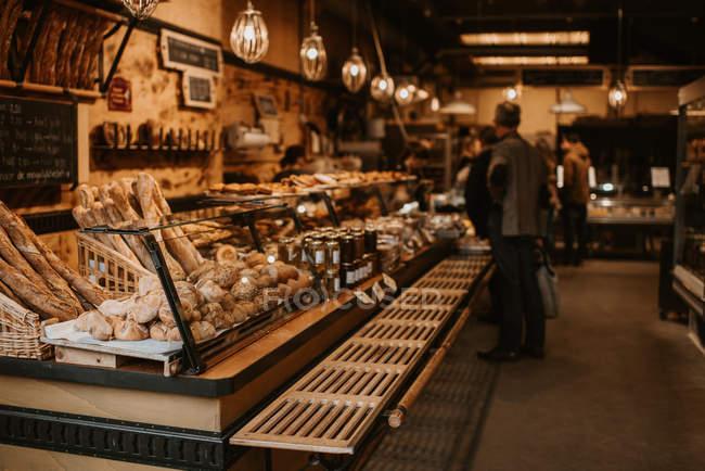 Personas en tienda de panadería, mostrador con masa vista en primer plano - foto de stock