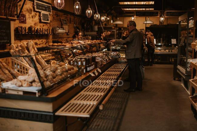 Pessoas na loja de padaria, balcão com vista para pastelaria em primeiro plano — Fotografia de Stock