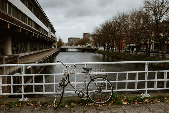 Bicycle parked by the Amsterdam city canal view — Stock Photo
