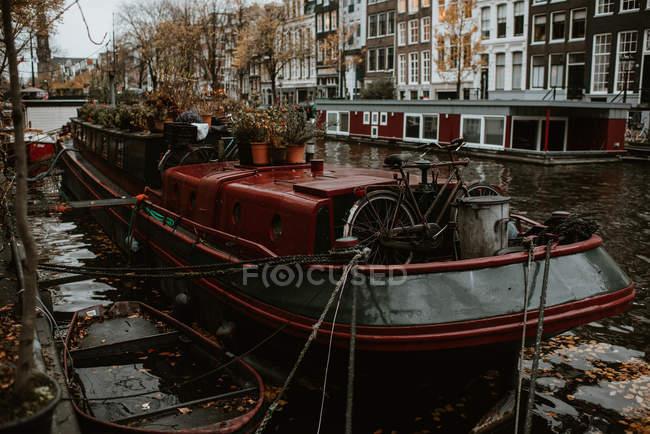 Famosa vista del paisaje urbano de Ámsterdam con arquitectura tradicional, canales y barcos amarrados - foto de stock