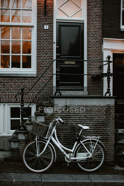 Typical dutch architecture and bicycle parked by house entrance, Amsterdam, Netherlands — Stock Photo