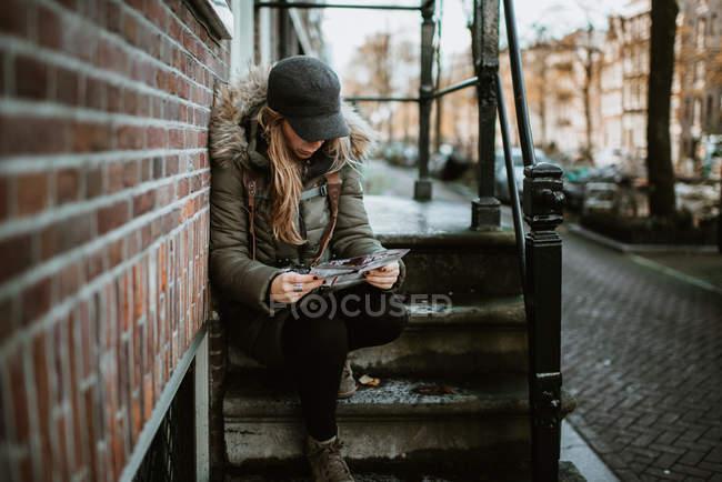 Frau sitzt auf der Treppe draußen auf der Straße auf der Suche auf Karte — Stockfoto