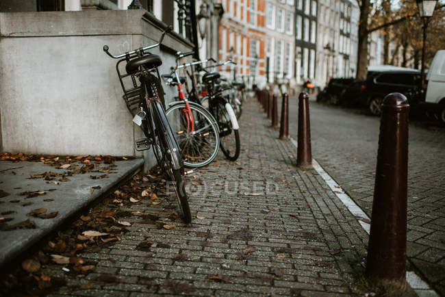 Bicycles parked in the row on one of Amsterdam streets — Stock Photo