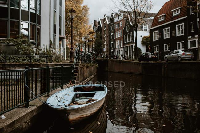 Amsterdam vista paisagem urbana com arquitetura tradicional, bicicletas, ponte sobre o canal e barco ancorado — Fotografia de Stock