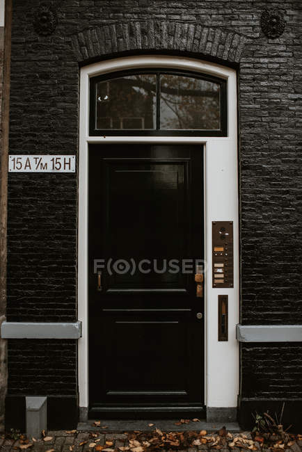 View of typical dutch house entrance with intercom by black wooden door — Stock Photo