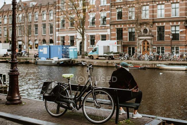 Вид сзади на молодого человека, сидящего на скамейке с велосипедом, смотрящего на Амстердам канал — стоковое фото